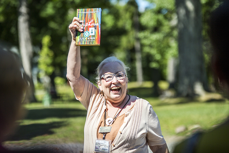 Sherra Babcock, vice president and Emily and Richard Smucker chair for education,  holds up the novel Euphoria by Lily King, one of the new Chautauqua Literary and Scientific Circle selections for next year, during the annual Bryant Day celebration in front of the Miller Bell Tower on August 22, 2015.