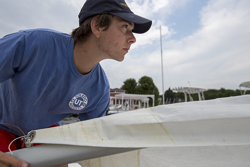 Sailing instructor Nick Rowe holds a sailboat boom Thursday, June 23, 2016, at the John R. Turney Sailing Center docks. The instructors were cleaning and rigging the boats in preparation for the start of the season.