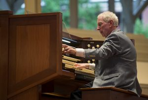 Jared Jacobsen plays the organ to accompany the Chautauqua Choir during the Sacred Song Service in the Amphitheater on Sunday, June 26, 2016.