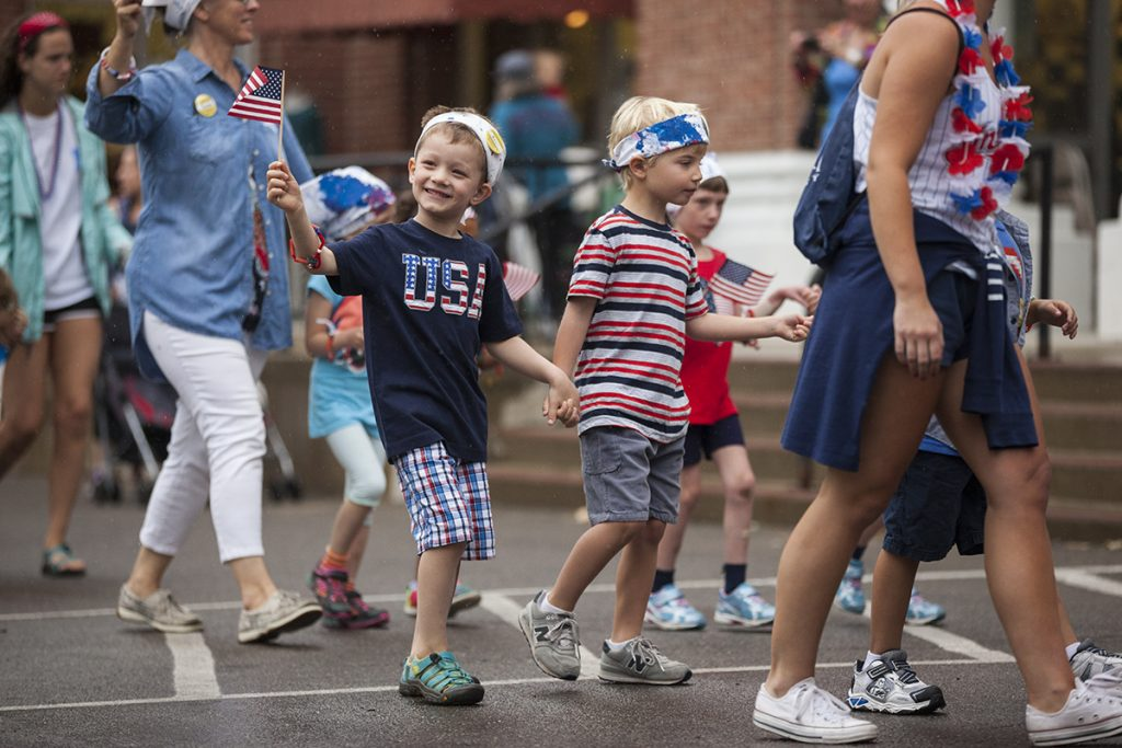 Arik Oskvig, left, five, waves an American flag to the crowd while walking toward the steps of the Colonnade on with Mason Arnold, right, five, on July 1, 2016. Oskvig and Arnold joined the other children and teachers of the Children's School to sing patriotic songs on the Colonnade steps and show off the patriotic apparel that they had made earlier that week. The parade was held on the Friday before the Fourth of July because the holiday officially falls on a Monday, which would give newcomers to Children's School no time to prepare for the parade. The parade was almost relocated due to rain, but the skies cleared up enough for the children to march to the Colonnade along their traditional parade route. Photo by Carolyn Brown.