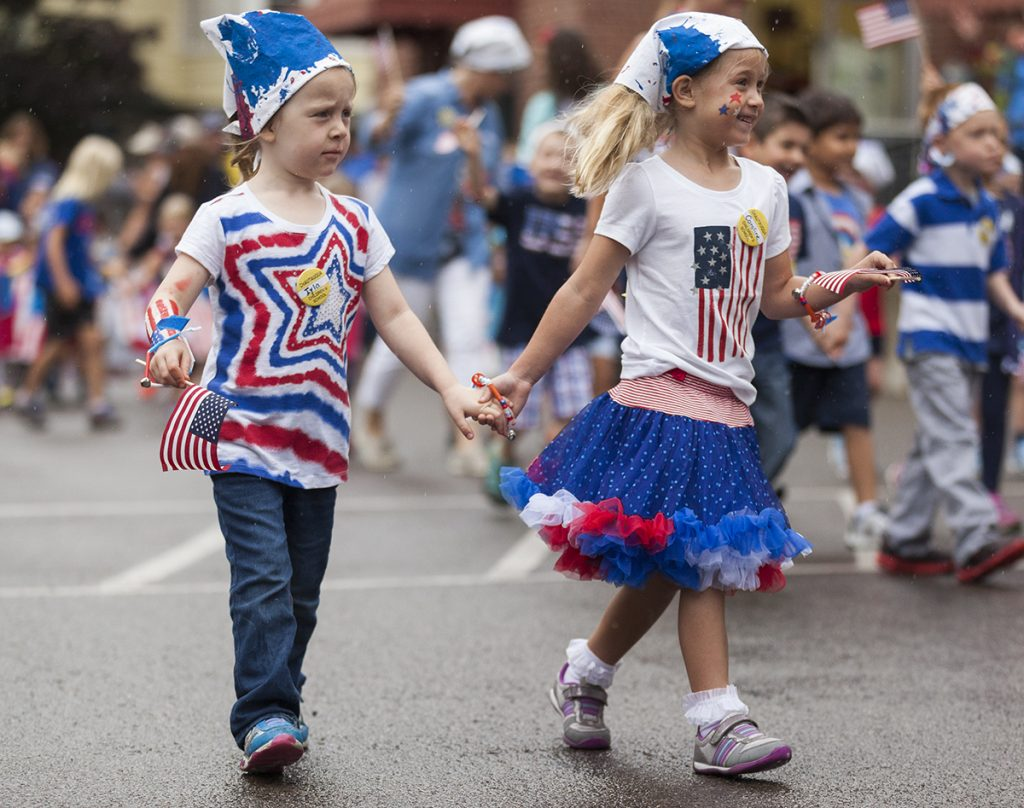 Iyla Vincent, left, five, and Caroline Kilpatrick, right, five, walk together towards the steps of the Colonnade on July 1, 2016, as part of the Children's School's annual Independence Day Parade. Vincent and Kilpatrick joined the other children and teachers of the Children's School to sing patriotic songs on the Colonnade and show off the patriotic apparel that they had made earlier that week. The parade was held on the Friday before the Fourth of July because the holiday officially falls on a Monday, which would give newcomers to Children's School no time to prepare for the parade. The parade was almost relocated due to rain, but the skies cleared up enough for the children to march to the Colonnade along their traditional parade route. Photo by Carolyn Brown.