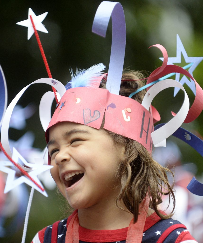 Hana Holland, 6, laughs as she walks in the annual Children's School Independance Day Parade Friday, July 1, 2016. Photo by Dave Munch.