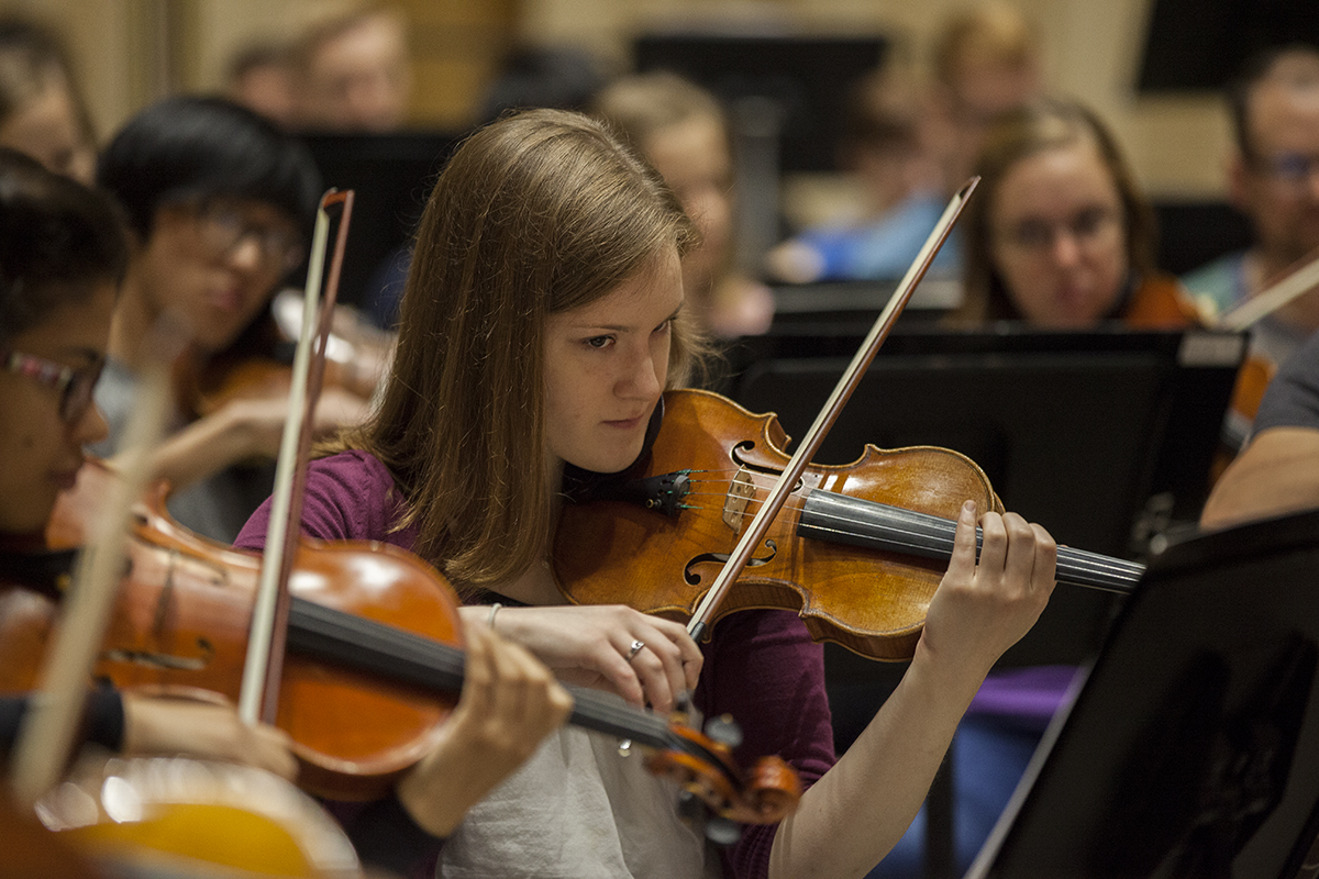 "Violinist Rachel Stenzel rehearses with the other members of the Music School Festival Orchestra in Lenna Hall on June 30, 2016. The entire MSFO will perform three pieces (Haydn's Symphony No. 2 in G Major, ""Oxford""; Mark Edwards Wilson's ""The Phoenix""; and Ravel's arrangement of Mussorgsky's ""Pictures at an Exhibition"") at the Amphitheater on Tuesday, July 5, at 8:15 PM. Photo by Carolyn Brown."
