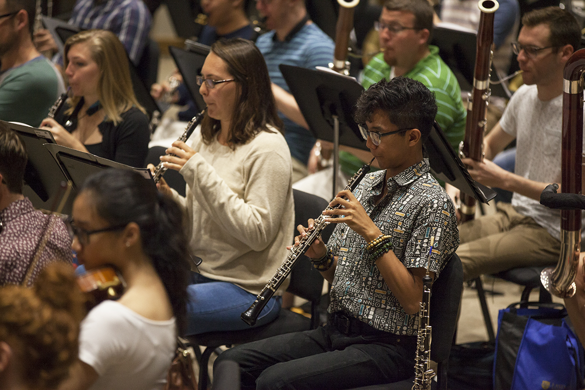 "Kevin Gupana plays his oboe during a rehearsal with the other members of the Music School Festival Orchestra in Lenna Hall on June 30, 2016. The entire MSFO will perform three pieces (Haydn's Symphony No. 2 in G Major, ""Oxford""; Mark Edwards Wilson's ""The Phoenix""; and Ravel's arrangement of Mussorgsky's ""Pictures at an Exhibition"") at the Amphitheater on Tuesday, July 5, at 8:15 PM. Photo by Carolyn Brown."