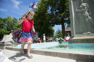 Lainey Vogel, 5, dances on the edge of the fountain during the Chautauqua Community Band 25th Annual Independence Day Concert in Bestor Plaza on July 4, 2016. Photo by: Sarah Holm