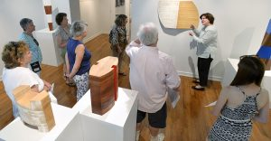 "Barbi Price, center right, descibes pieces in the exhibit ""Shape of Things to Come"" by Kevin O'Toole while leading visitors on a tour through Strohl Art Center Wednesday, July 6, 2016."