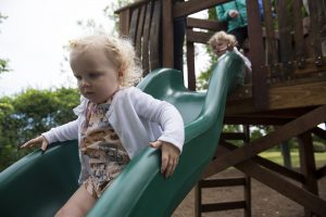 Millie Grant, 2, glides down a slide at Timothy's Playground after the dedication ceremony on July 2, 2016. The playground was created in memory of Timothy Ritacco who passed away in 2004. The benches, toy car, log tunnel and stumps were all created using trees that needed to be cut down around the grounds.
