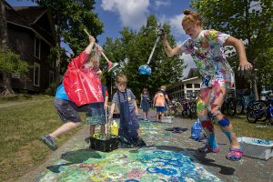Connor Ewalt, left and Katherin Clark use plungers as paintbrushes during the Big Art Everywhere activities Wednesday, July 6, 2016, at the Children's School.