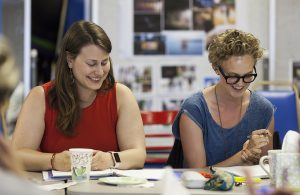 "Playwright Chelsea Marcantel, left, and actor Anna Tullis, right, laugh during a table reading of Marcantel's ""Tiny Houses,"" one of the upcoming plays in the Chautauqua Theater Company's New Play Workshop, at 4:30 PM on July 11, 2016, in Studio B at Brawdy Theater Studios. Marcantel plays the character Jevne, who makes a living producing ASMR videos online. Photo by Carolyn Brown."