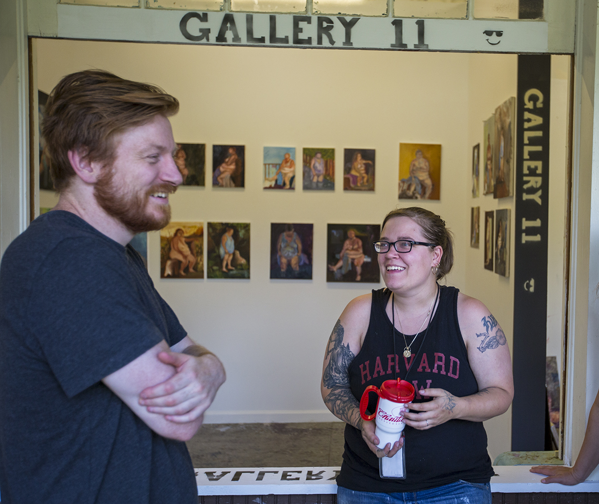 School of Art students David Dupak and Sarah Jarrett chat in front of Gallery 11 where some of their paintings are displayed Monday, July 11, 2016, at the School of Art.