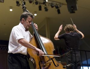 "Bassist Edgar Meyer, left, plays ""Concerto for Double Bass in D (1993)"" as conductor Teddy Abrams, right, leads the Chautauqua Symphony Orchestra at their 8:15 PM concert on July 14, 2016, in the Amphitheater. Meyer, who composed the piece himself, returned to the stage for two encores after playing the piece. Photo by Carolyn Brown."