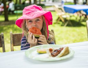 Caroline Kilpatrick, 4, eats watermelon during the Great American Picnic sponsored by the Chautauqua Literary and Scientific Circle Alumni Association in the front lawn of Alumni Hall July 19, 2015.