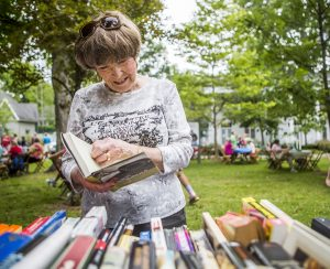 Kathy Richardson browses the book sale during the Great American Picnic sponsored by the Chautauqua Literary and Scientific Circle Alumni Association in the front lawn of Alumni Hall July 19, 2015.