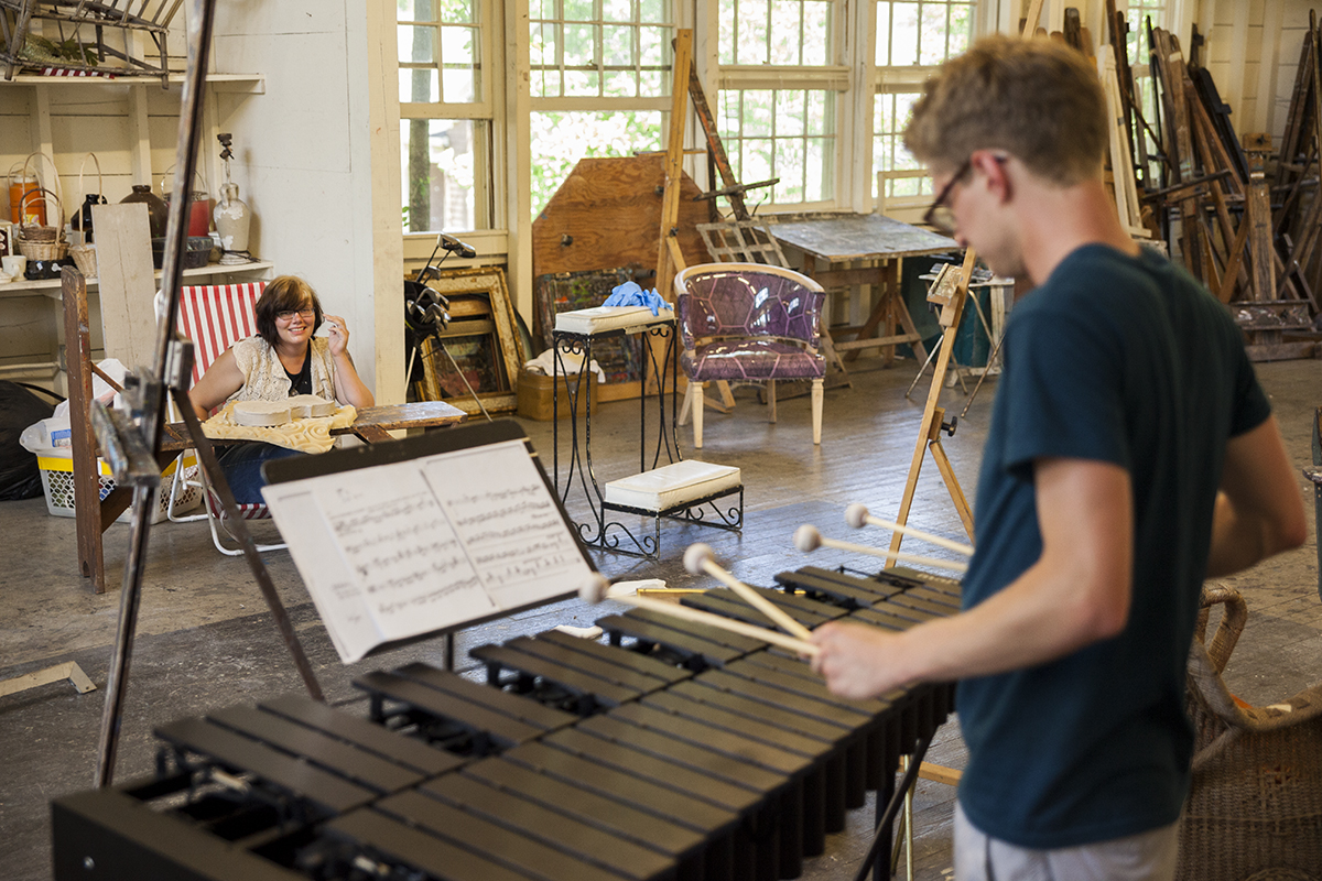 "Alex Myers, left, looks up from carving a porcelain violin as Julian Loida, right, plays John Cage's ""Dream (Music for the Dance by Merce Cunningham)"" on the vibraphone at 3 PM on July 13, 2016, at the School of Art. Loida oversees the Chautauqua Inter-Arts Collective, which brings together students from the Schools of Art, Music, and Dance, to share their work and inspire their peers. This is the first year that the program is student-run. Photo by Carolyn Brown."