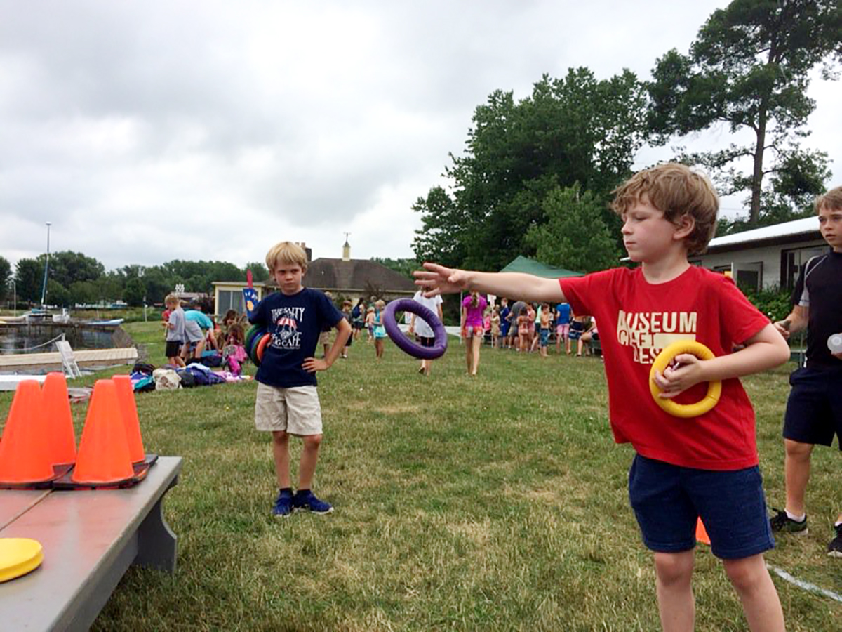 Dash Bauer of Group 2 Boys tries his hand at the ring toss event during Club Carnival on Wednesday.