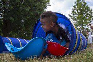 Jamille Harvey, 5, crawls out of a tube while competing on the obstacle course during Wacky Water Day on Wednesday, July 13, 2016, at Children's School.