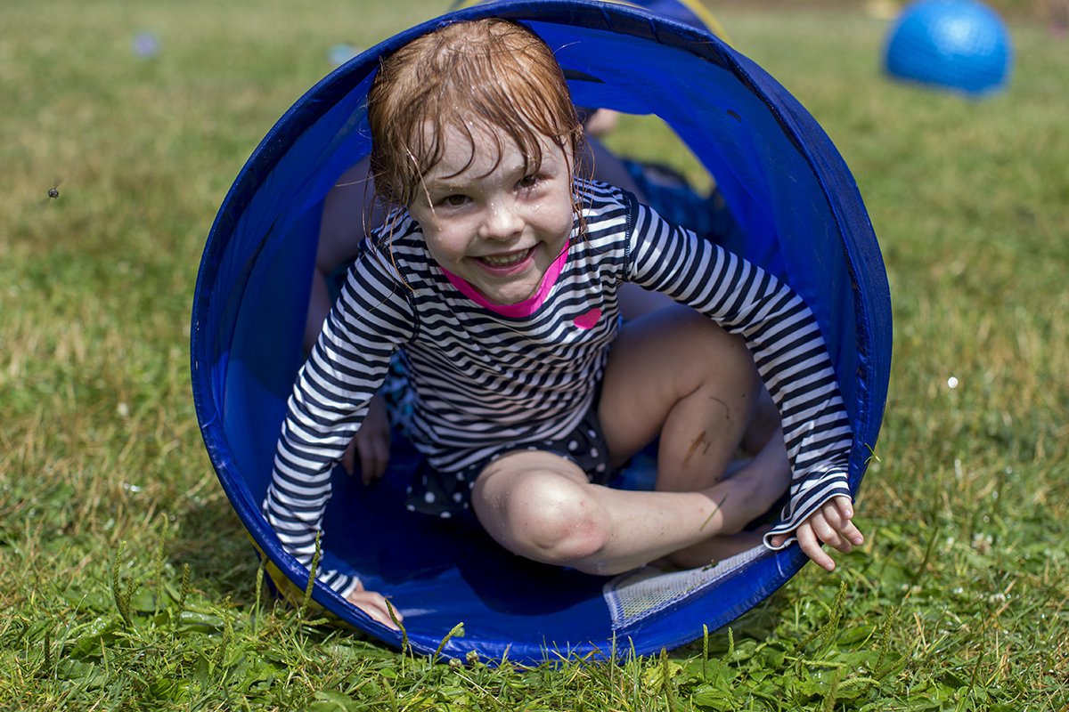 Madi Cooper, 4, crawls out of a tube during Wacky Water Day on Wednesday, July 13, 2016, at Children's School.