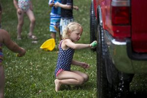 Addison Steere cleans a car during Wacky Water Day on Wednesday, July 13, 2016, at Children's School.