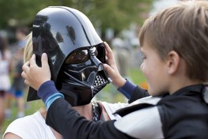 Astrid Weismann wears the Darth Vader mask from her son Rhys Weismann's, 5,  costume during the Star Wars costume contest before the screening of The Force Awakens on Tuesday, July 19, 2016, at Bestor Plaza.