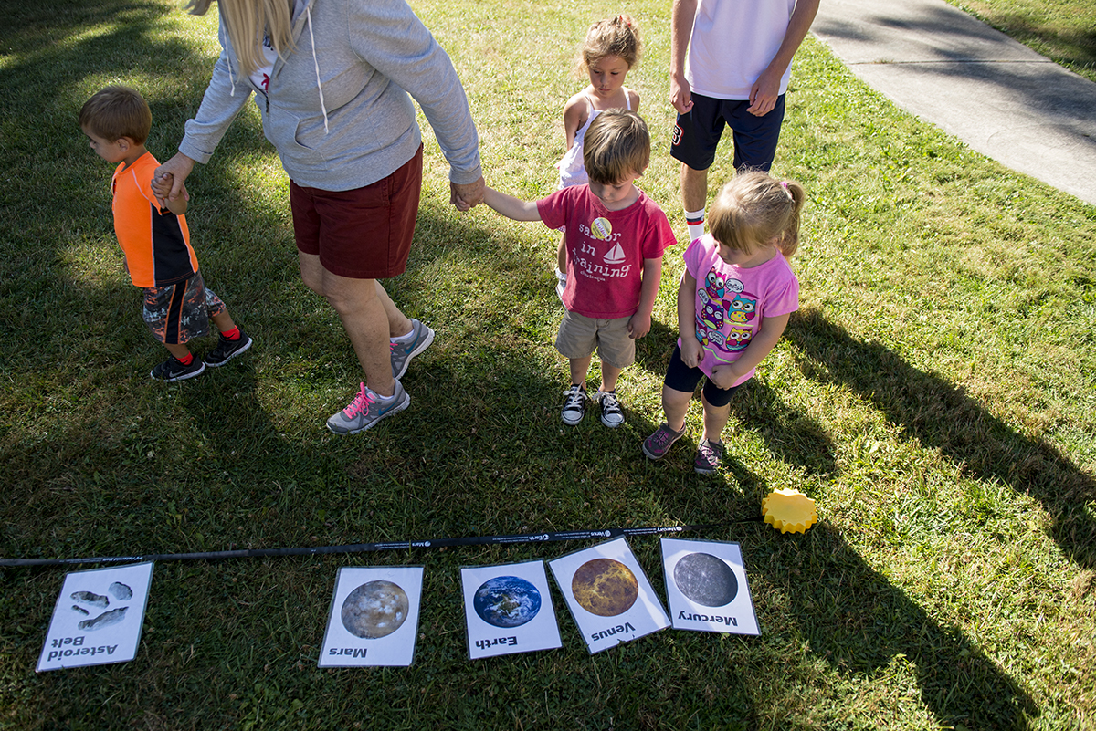 Children walk along a simulation of how far away the planets are from the sun. Stephanie Kohser and Aly Toy from the Carnegie Science Center gave a presentation about outer space at Children's School on July 21, 2016. Photo by Sarah Holm