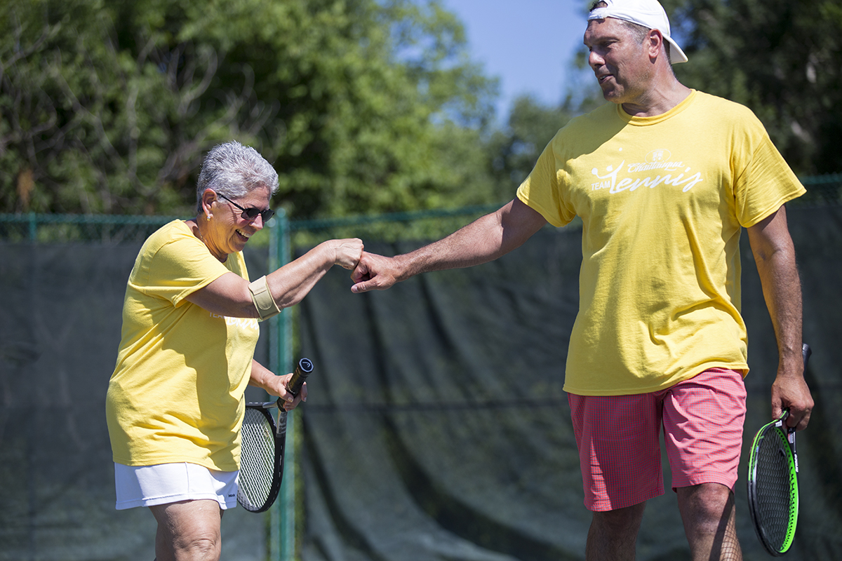 Judy Williams fist bumps her teammate Karan Chopra during the team tennis tournament Saturday, July 23, 2016, at the Chautauqua Tennis Center. Photo by: Mike Clark