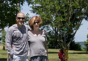Jon and Joan Hackett, son and wife of Jerome C. Hackett, stand in front of a tree planted in Jerome's honor in Miller Park.