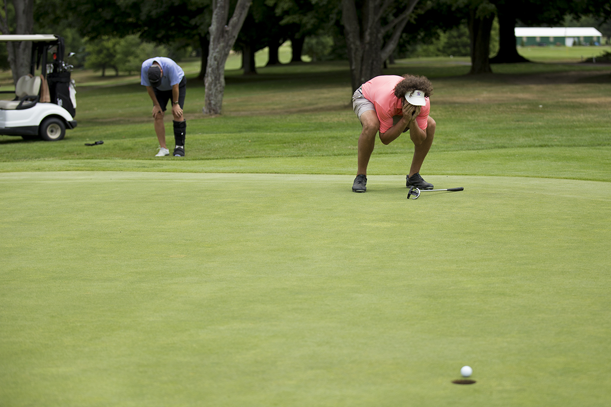 Ben McCauley, right, reacts with his father Jack McCauley as his ball stops just short of an eagle on the 18th hole during the Men's Member Guest Golf Tournament on Sunday, July 24, 2016, at the Chautauqua Golf Club. Photo by: Mike Clark