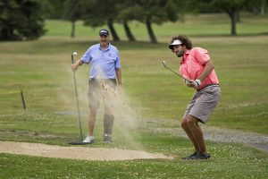 Ben McCauley, hits out of a sand trap as his father Jack McCauley watches during the Men's Member Guest Golf Tournament on Sunday, July 24, 2016, at the Chautauqua Golf Club. Photo by: Mike Clark