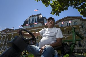 Jim McCann is part of the grounds crew that tends the lawn in front of the Athenaeum Hotel.