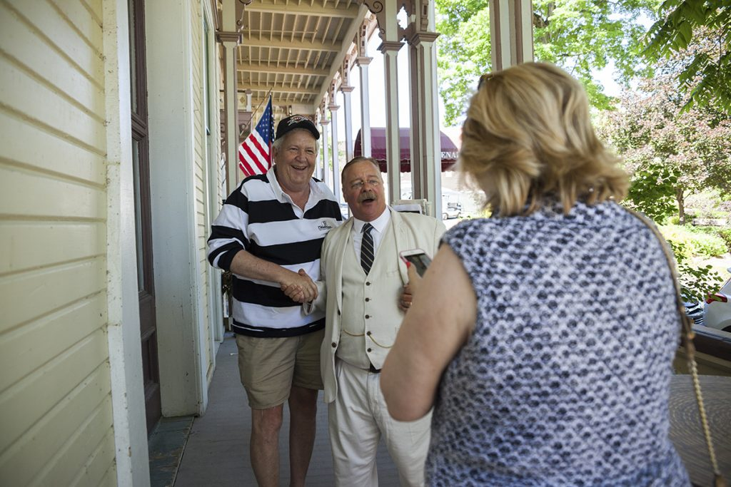 Mike Turpen, left, poses for a photo with Joe Wiegand as his wife, Susan, right, gets her phone camera ready at 11 AM on the Athenaeum porch.  Wiegand's talk was part of the Turpens' first ever visit to Chautauqua. Photo by Carolyn Brown.