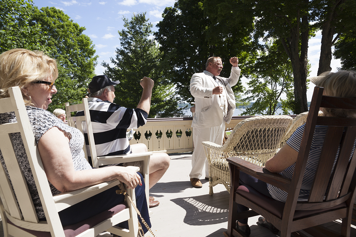 "Joined eagerly by Susan Turpen, left, and Mike Turpen, center left, Theodore Roosevelt impersonator Joe Wiegand leads audience members in three cheers for Chautauqua at the end of his talk at 10 AM on the Athenaeum porch on June 28, 2016. Earlier in his presentation, Wiegand recalled a quote from Roosevelt, who once called Chautauqua ""the most American place in America."" Photo by Carolyn Brown."