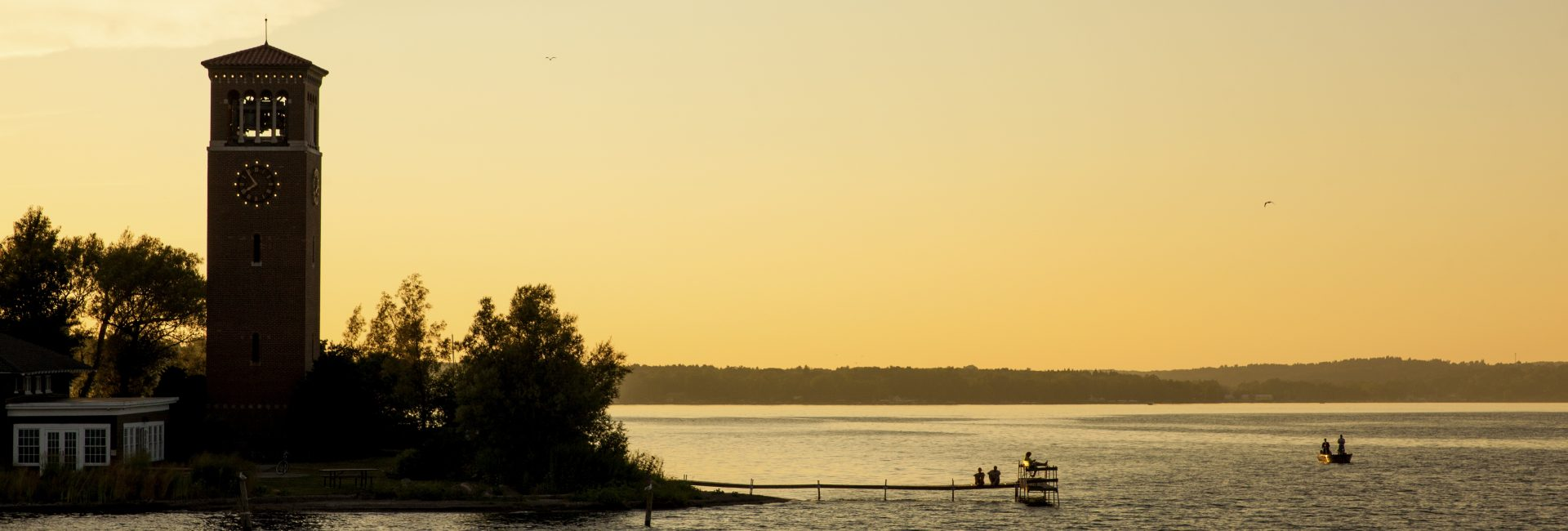 Chautauquans enjoy a sunset on the shore at 8 P.M. on Wednesday, August 10, near the Bell Tower. Photo by Carolyn Brown.
