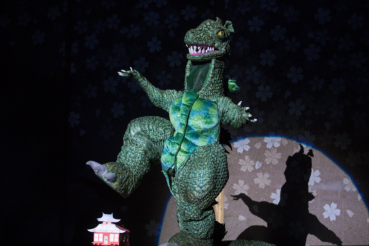 "Godzilla crushes a house in the opening scene of the dress rehearsal for ""The Mikado"" on Wednesday, July 27, 2016, in Norton Hall. Photo by: Mike Clark"