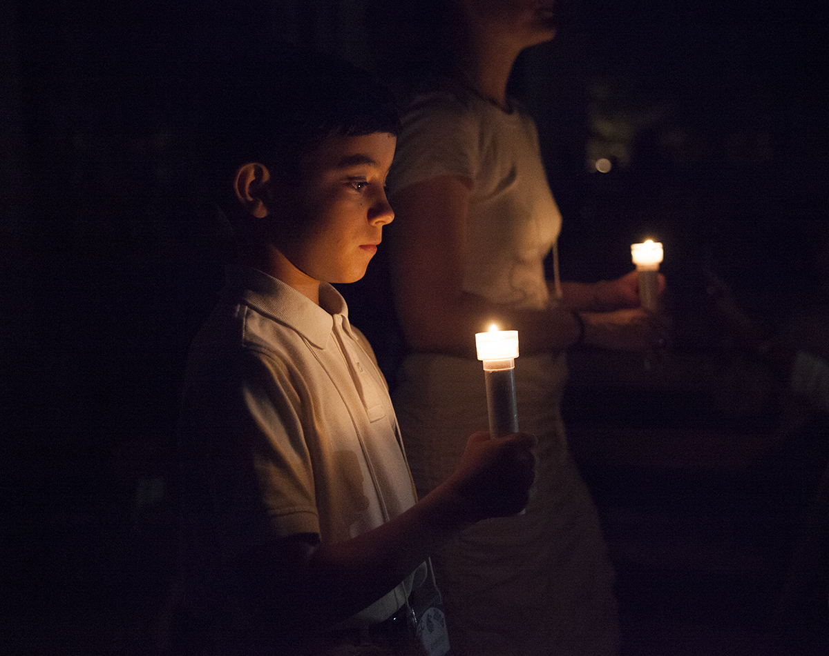 "Paul Ritacco III, 10, walks in the Class of 2016 Candelight Vigil at 9 PM on Sunday, July 31, 2016, outside Alumni Hall. During the ceremony, Ritacco also a reading from John Heyl Vincent's ""The Chautauqua Movement."" Photo by Carolyn Brown."