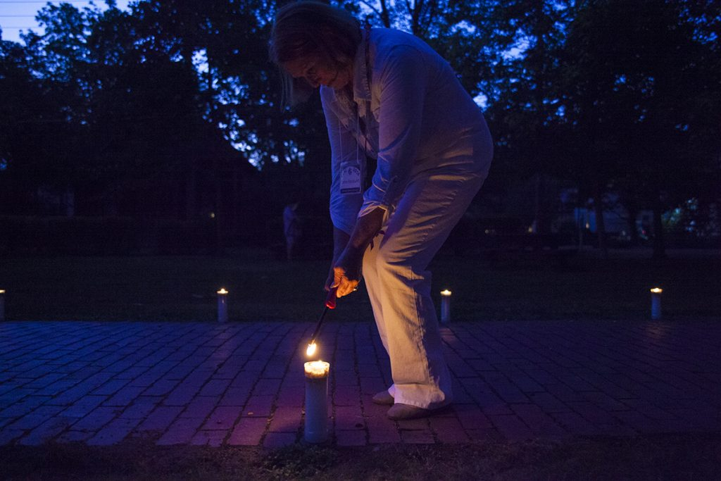 Cathie Backlund lights a candle before the Class of 2016 Candelight Vigil at 9 PM on Sunday, July 31, 2016, outside Alumni Hall. The Vigil is akin to a graduation ceremony and honors the members of the new CLSC class. Photo by Carolyn Brown.