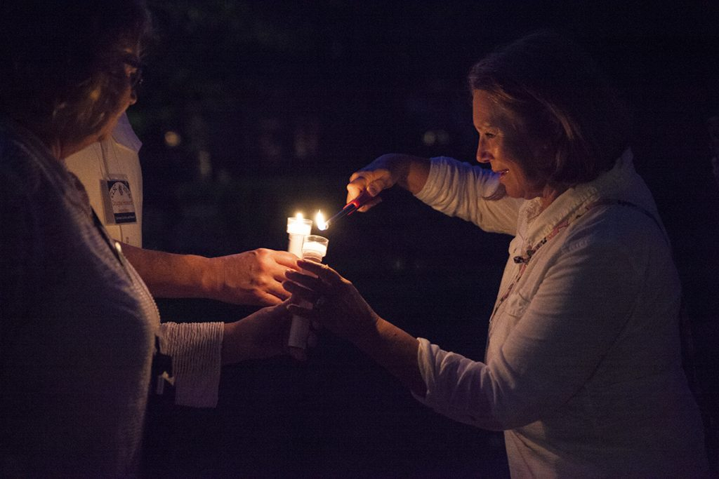 Cathie Backlund, right, lights candles for members of the CLSC Class of 2016  before the Class of 2016 Candelight Vigil at 9 PM on Sunday, July 31, 2016, outside Alumni Hall. The Vigil is akin to a graduation ceremony and honors the members of the new CLSC class. Photo by Carolyn Brown.