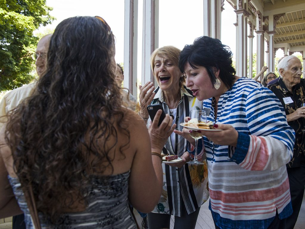 Kristin Currin, left, shows her phone to Linda Steckley, center, and Tina Downey, right, at the Volunteer Recognition Party at 5:30 P.M. on Tuesday, July 26, 2016, on the Athenaeum Hotel Porch. The event included a special presentation by the day's morning lecturer, Nalini Nadkarni. Photos by Carolyn Brown.
