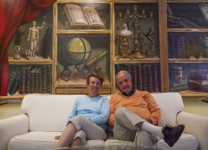 Joanne and Paul Anthony Ritacco pose for a portrait at noon on Tuesday, August 23, 2016, in their home at 52 Foster. The Ritaccos said that the mural they are sitting in front of contains representations of the various facets of Chautauqua, including religion and education. Photo by Carolyn Brown.
