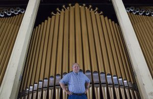 "Paul Fischer poses for a portrait at 4:30 P.M. on Friday, August 19, 2016, in front of the Massey Organ. Fischer is the author of a book called ""Making Music"" and has overseen renovations of the Massey Organ.  Photo by Carolyn Brown."