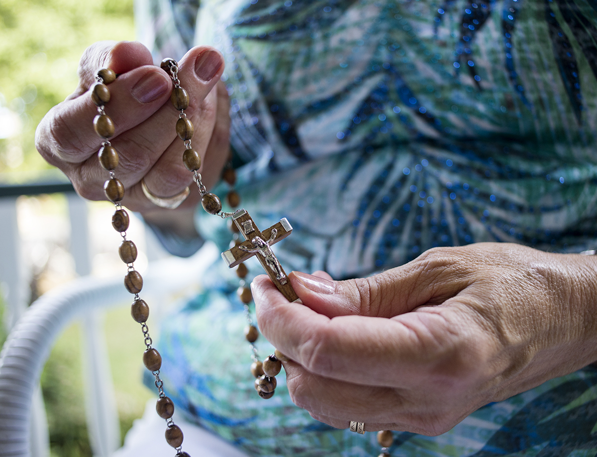 Susan Drabant demonstrates the meaning behind the beads of her rosary outside the Catholic House August 24, 2016.
