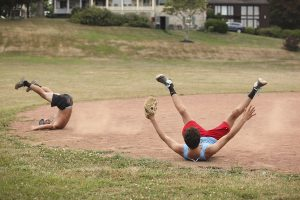 Skyler Zarou, left, and Peter Evans, right, members of the YAC PAC softball team, fall backwards after colliding in a celebratory mid-air body bump in honor of their softball team's victory over the Slugs team at 7 PM on Friday, July 29, at Sharpe Field. The YAC team beat the Slugs 21-5. Photo by Carolyn Brown.