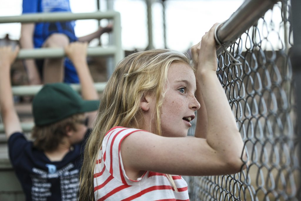 Madeline Steere, 10, watches the final game in the men's softball league from the Slugs team dugout at 7 P.M. on Wednesday, August 3, 2016, at Sharpe Field. The Slugs team, whom Steere was rooting for, beat the YAC PAC team 38-11. Photo by Carolyn Brown.