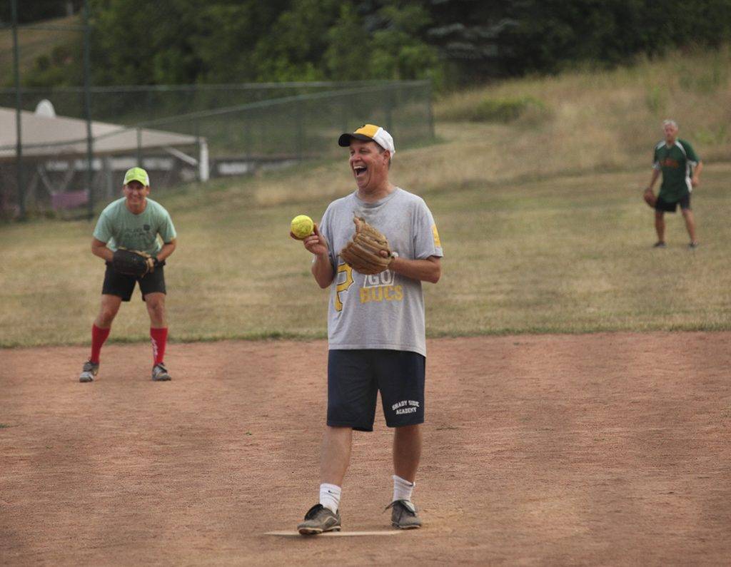 Pitcher Jeff Miller, of the Slugs team, center, laughs before throwing out a pitch to the YAC PAC team at 8 P.M. on Friday, July 29, 2016, at Sharpe Field. Photo by Carolyn Brown.