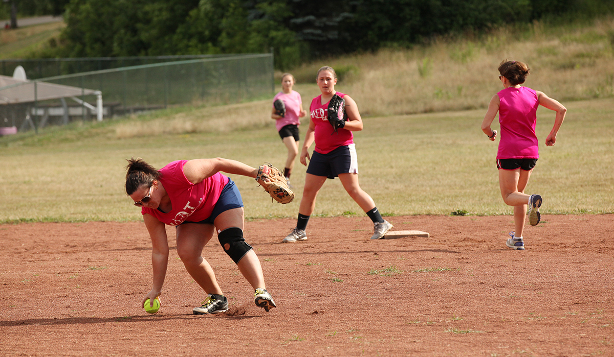 Maureen Gray, left, of the Hot Chauts softball team, picks up a ball at a game between the Hot Chauts and the Chautauqua Belles at 5 PM on Sunday, July 31, 2016, at Sharpe Field. Photo by Carolyn Brown.